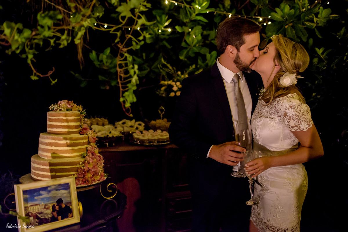 retrato do casal em beijo em frente a mesa de doces Bruna Doces com bolo Ana Petryna e decoração Casa Branca Eventos