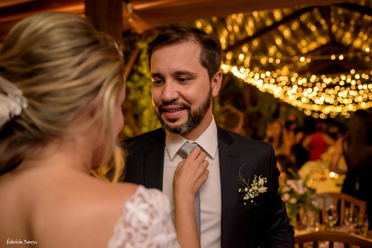 noiva ajusta gravata do noivo durante pequeno casamento intimista