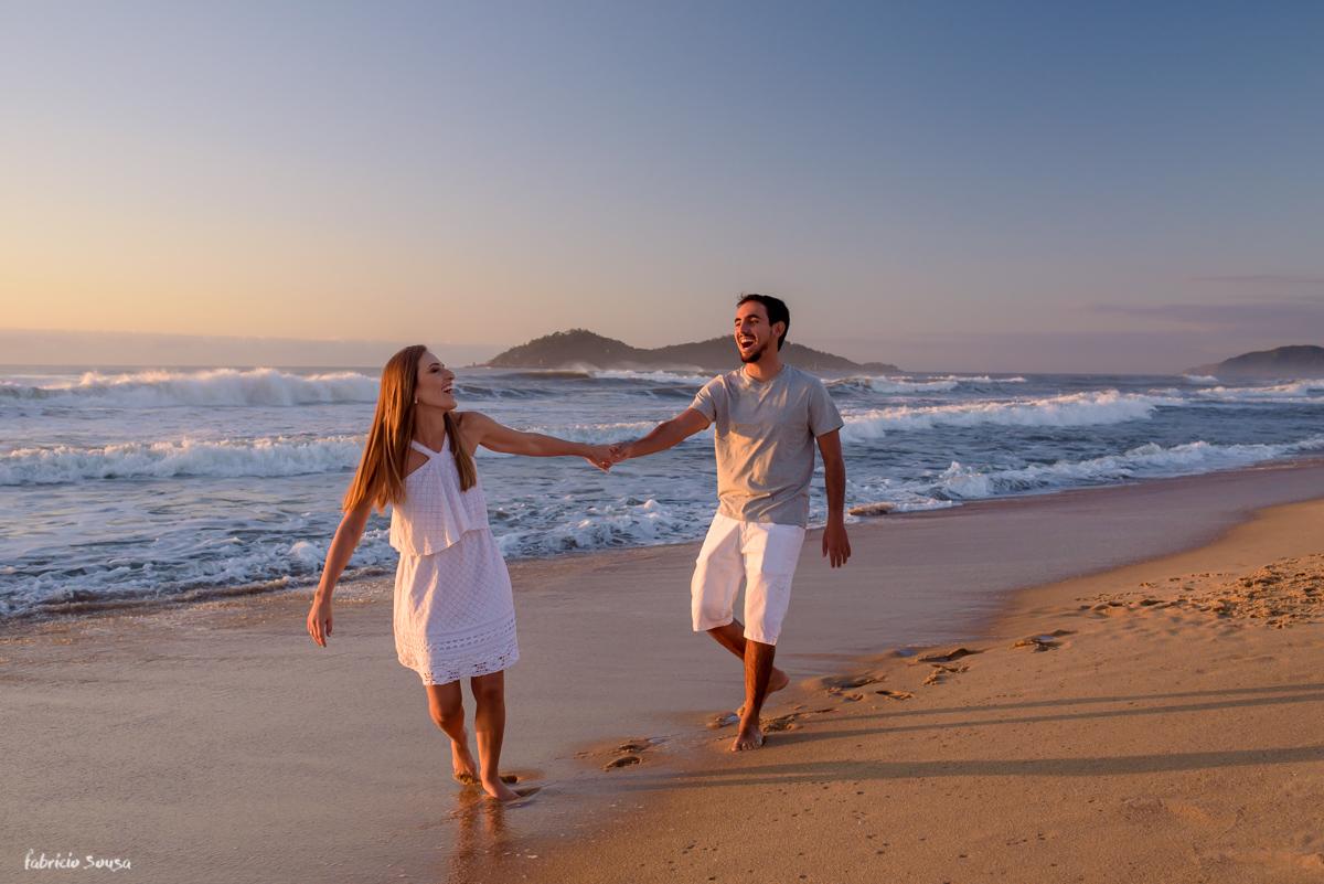 noiva puxando noivo na areia da praia do Campeche em Floripa