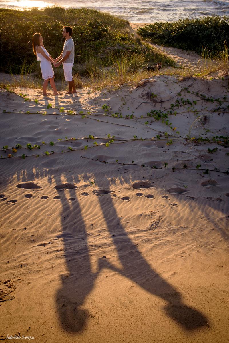 sombra projetada do casal de mãos dadas namorando na restinga da praia em Floripa