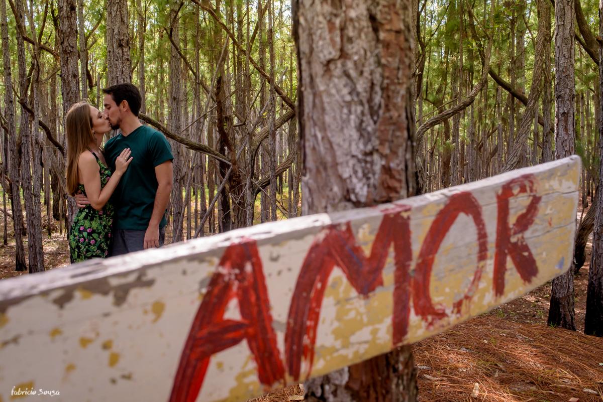 casal se beijando com placa escrito amor no bosque com luz dourada - ensaio prewedding