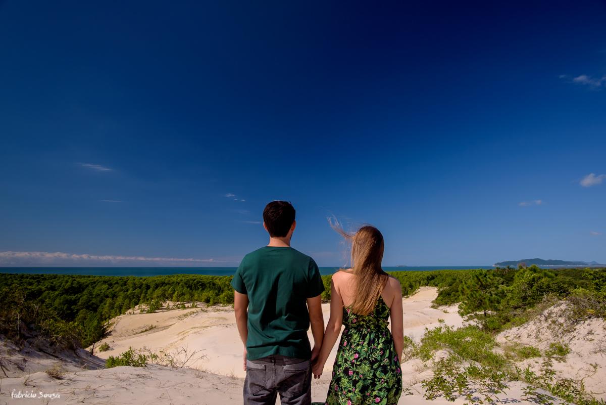 casal de mãos dadas apreciando a vista da praia do Moçambique Costão das Aranhas Floripa