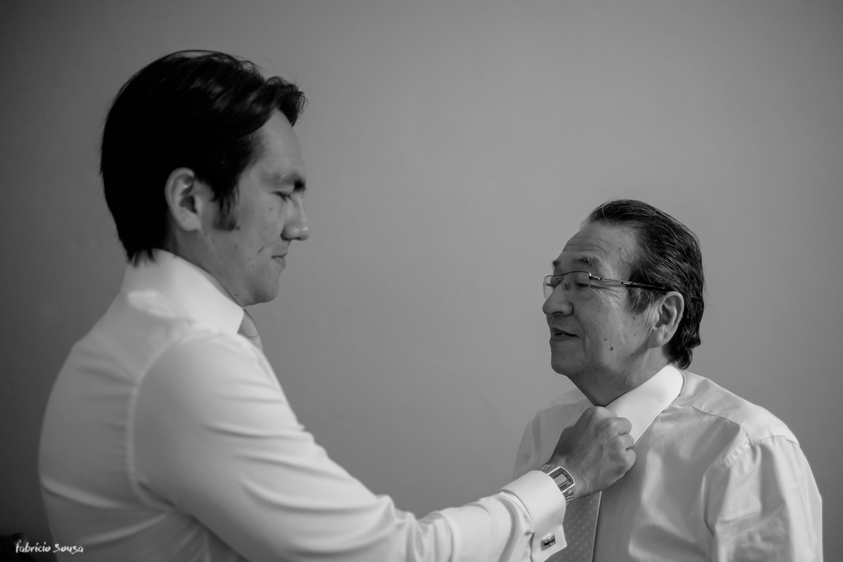 filho arruma gravata do pai durante making of de casamento