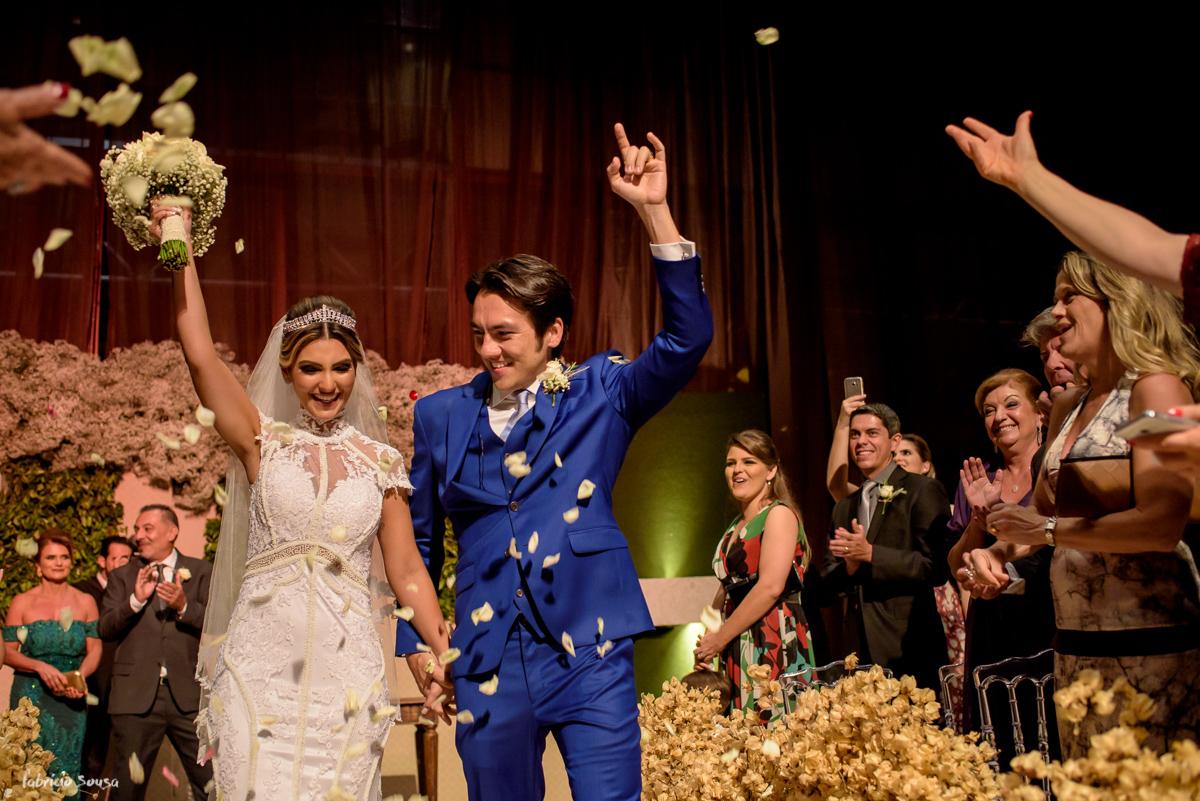 noivo fernando roqueiro faz sinal do metal e noiva Fernanda levanta o bouquet na saída da cerimonia no Estação das Docas com pétalas brancas