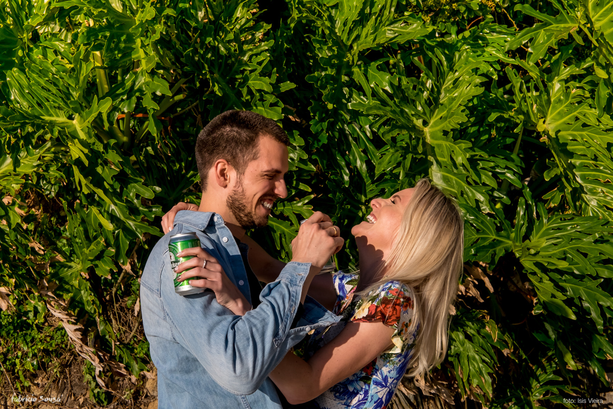 casal bebendo cerveja durante ensaio prewedding na praia