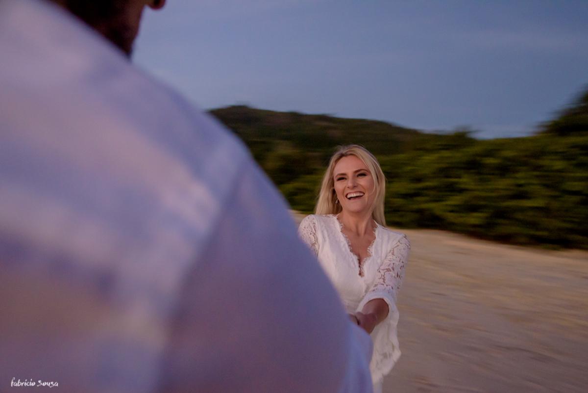 noivos brincando na praia durante sessão de fotos de casal