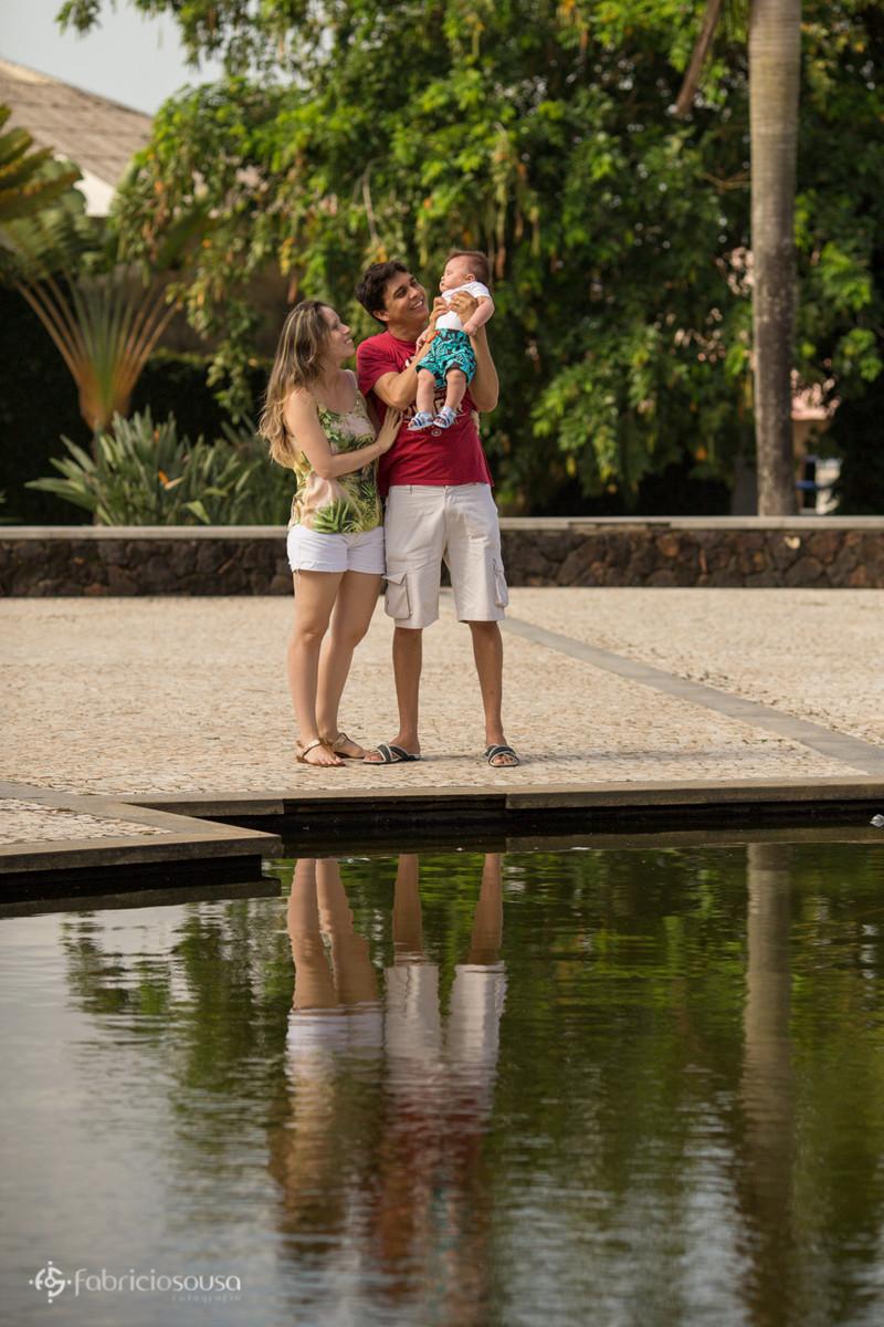 Pai segura Heitor ao lado da mãe na beira da água da praça