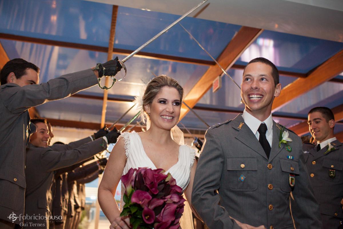 noivos sorridentes na saída da cerimonia com teto de aço - espadas ao ar