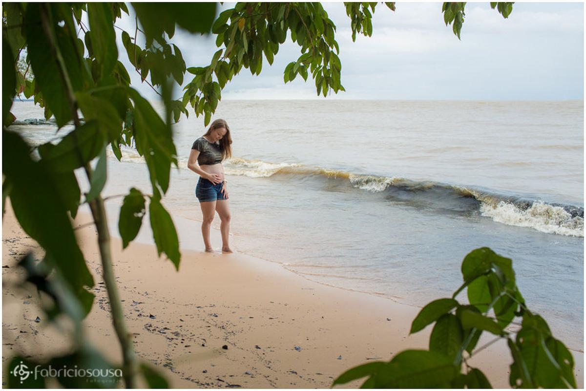 Gestante com os pés na água da praia