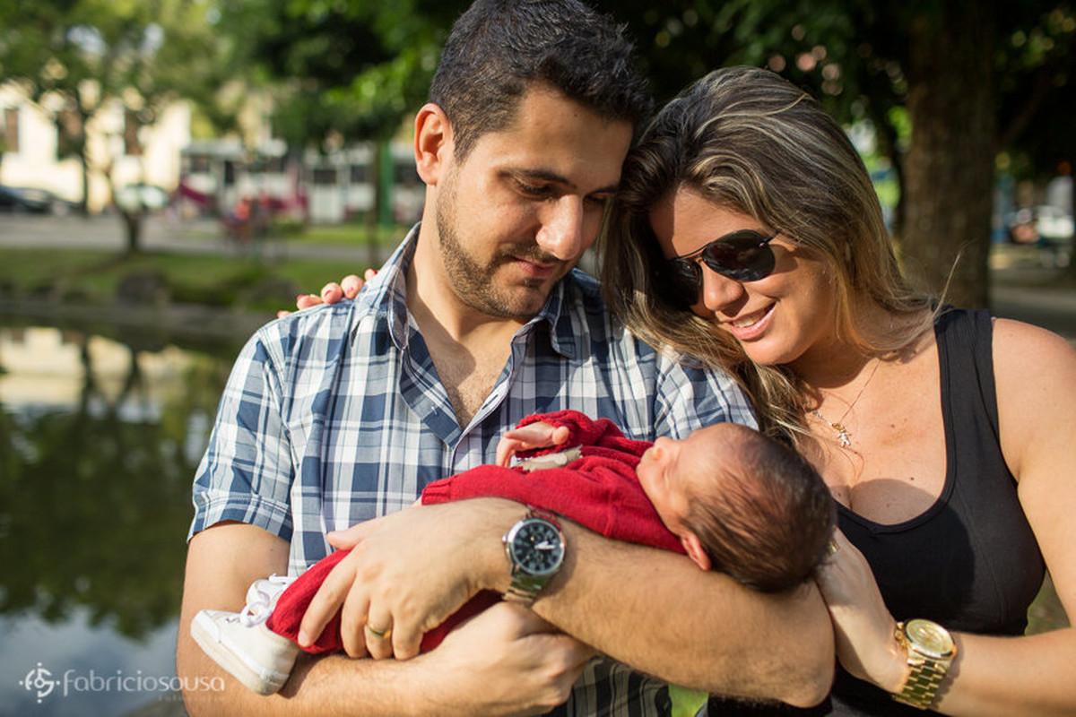 Paí segura Miguel e mãe ao lado aprecia o filho