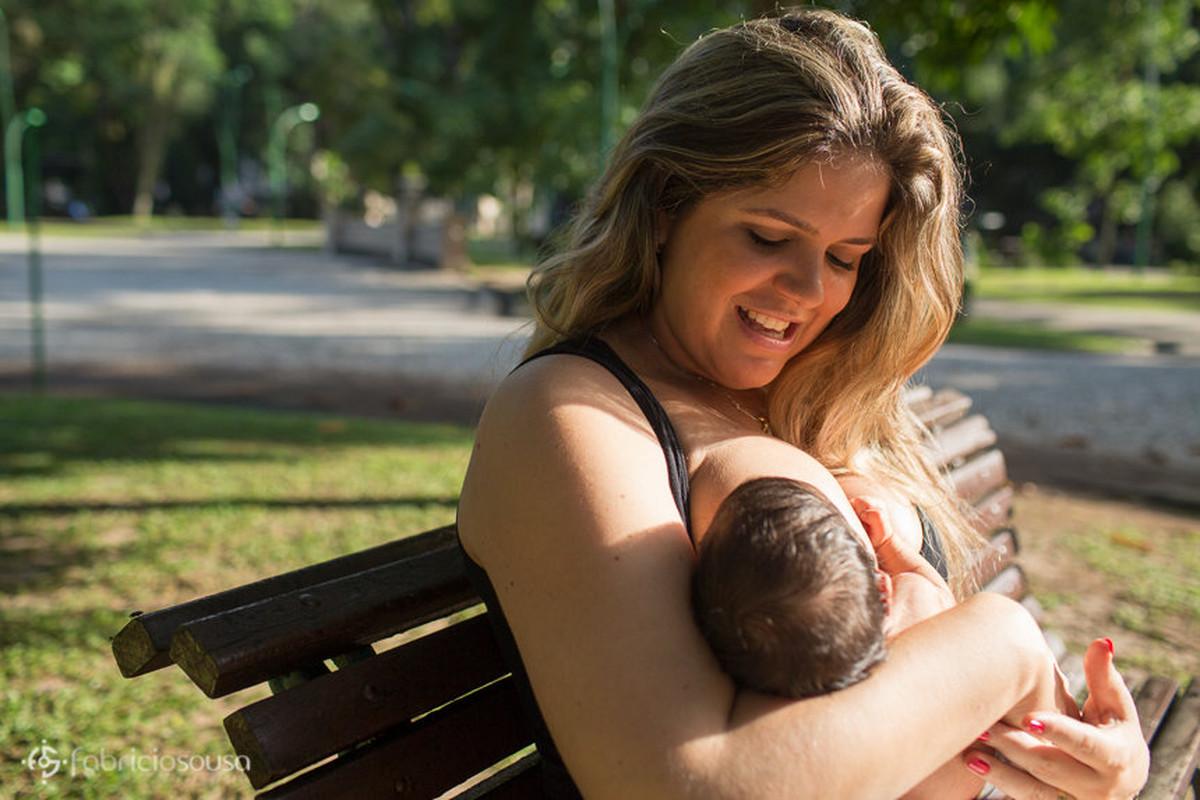 Miguel aproveita pra mamar direto do seio da mãe sentada em banco na praça