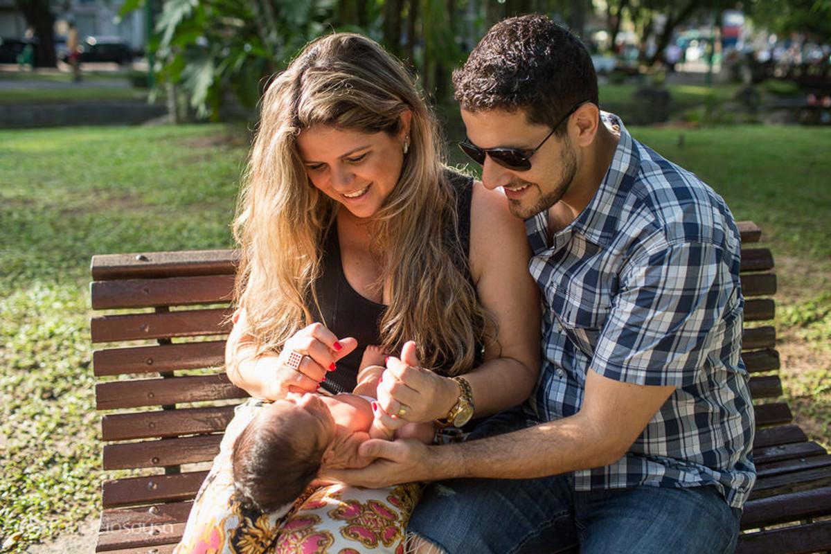 Dani e Leo sentados no banco da praça com o pequeno Miguel