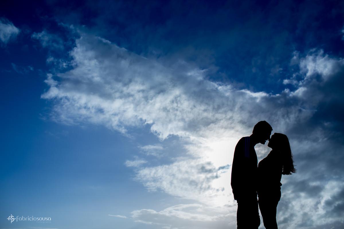 silhueta do casal quase se beijando com céu azul e muitas nuvens