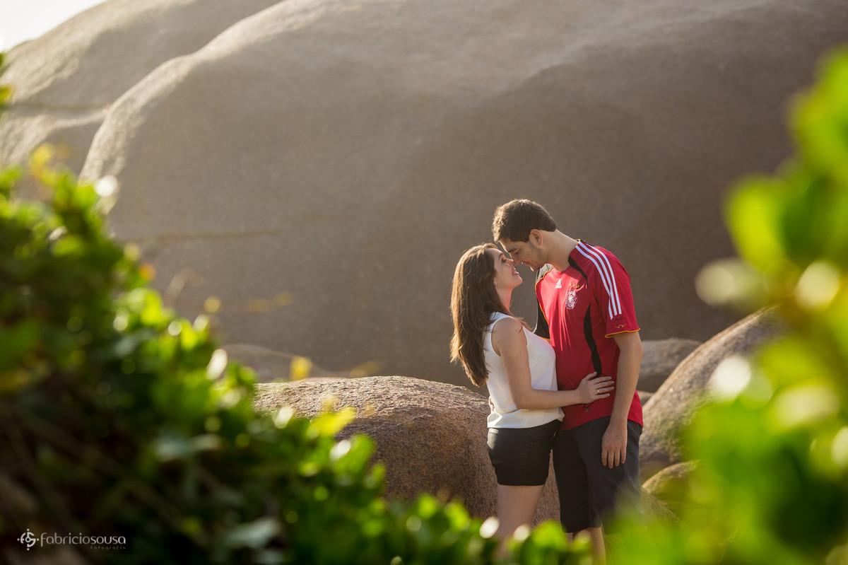 em meio às pedras o casal se abraçam apaixonados encostando os narizes e o sol nascente os ilumina enquanto o fotógrafo registra esse pre-wedding atrás das folhas numa cena romântica em Florianopolis