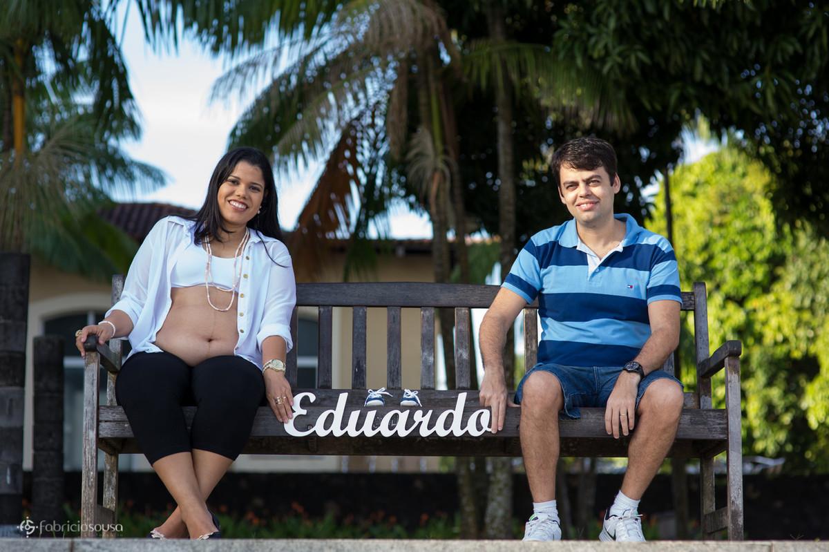 Mãe e pai seguram sentados a placa do nome do filho