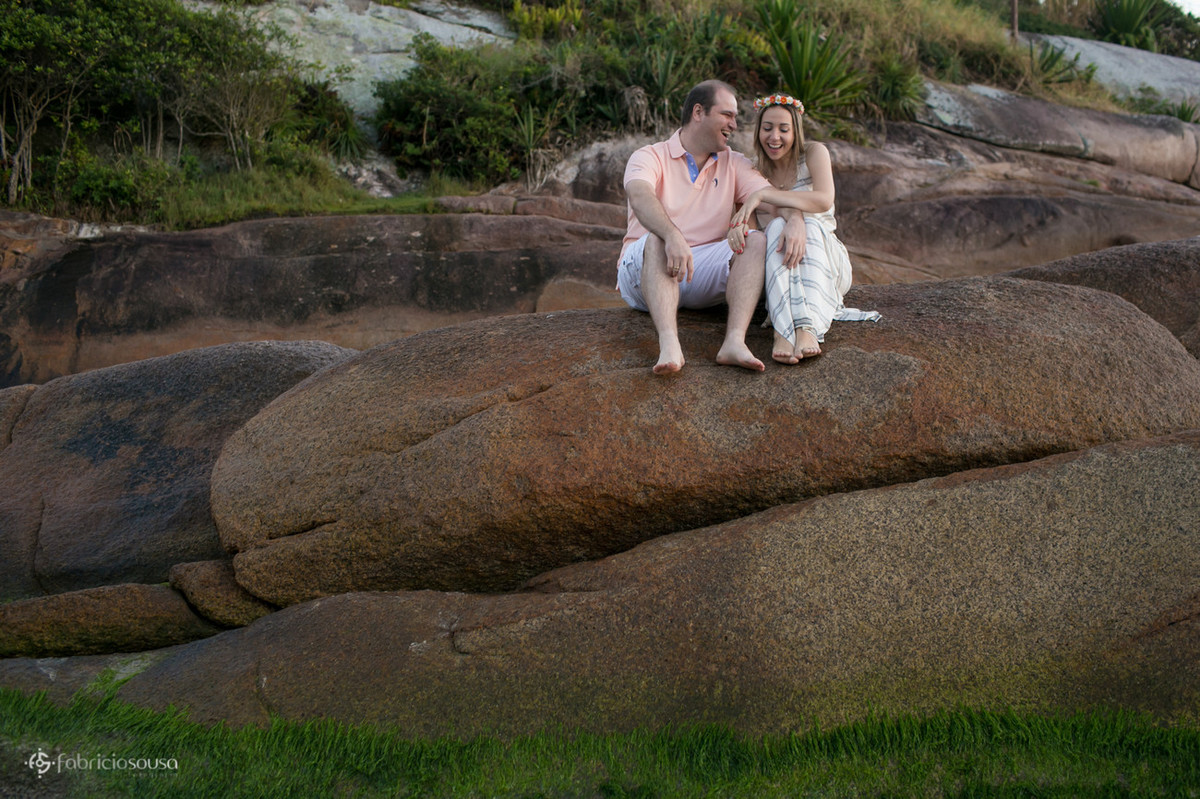 casal rindo em cima da pedra na praia da Barra da Lagoa