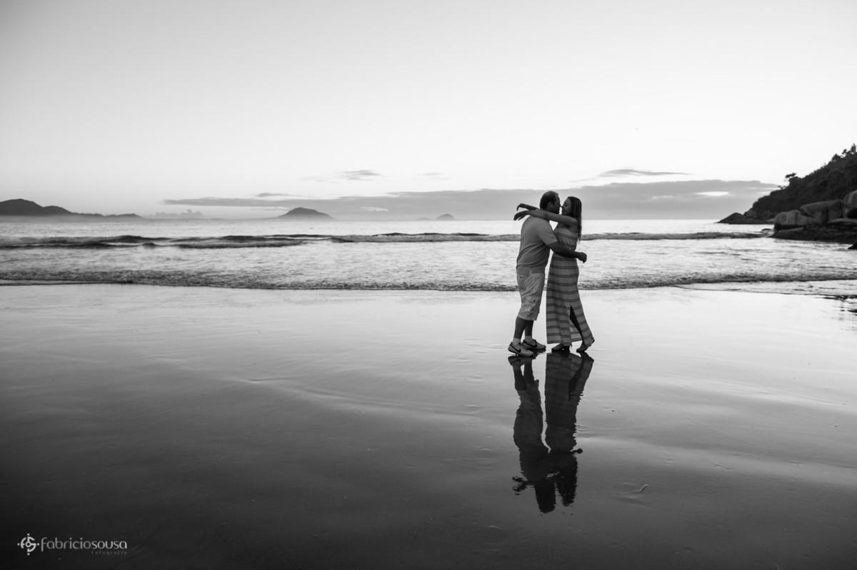 espelho d'água na areia da praia com casal se beijando