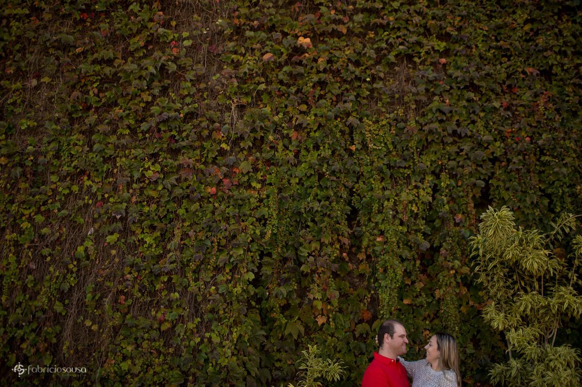 casal namorando na frente do muro vivo