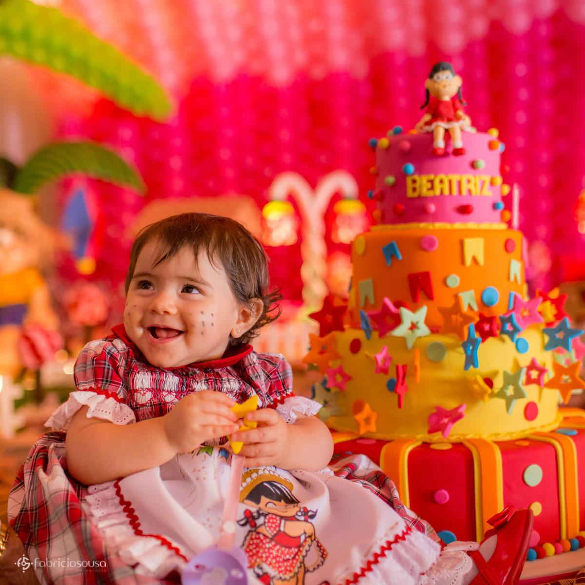 Beatriz de 1 ano ao lado do bolo de aniversário de 4 andares