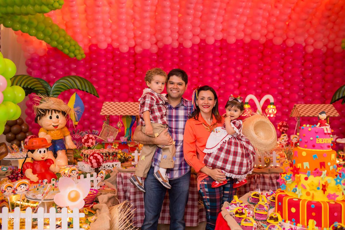 Retrato da família em frente a mesa de doces
