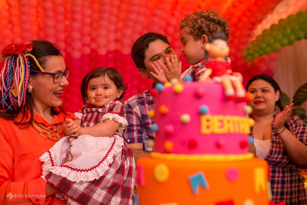 Mãe, aniversariante, pai e irmão atras do bolo