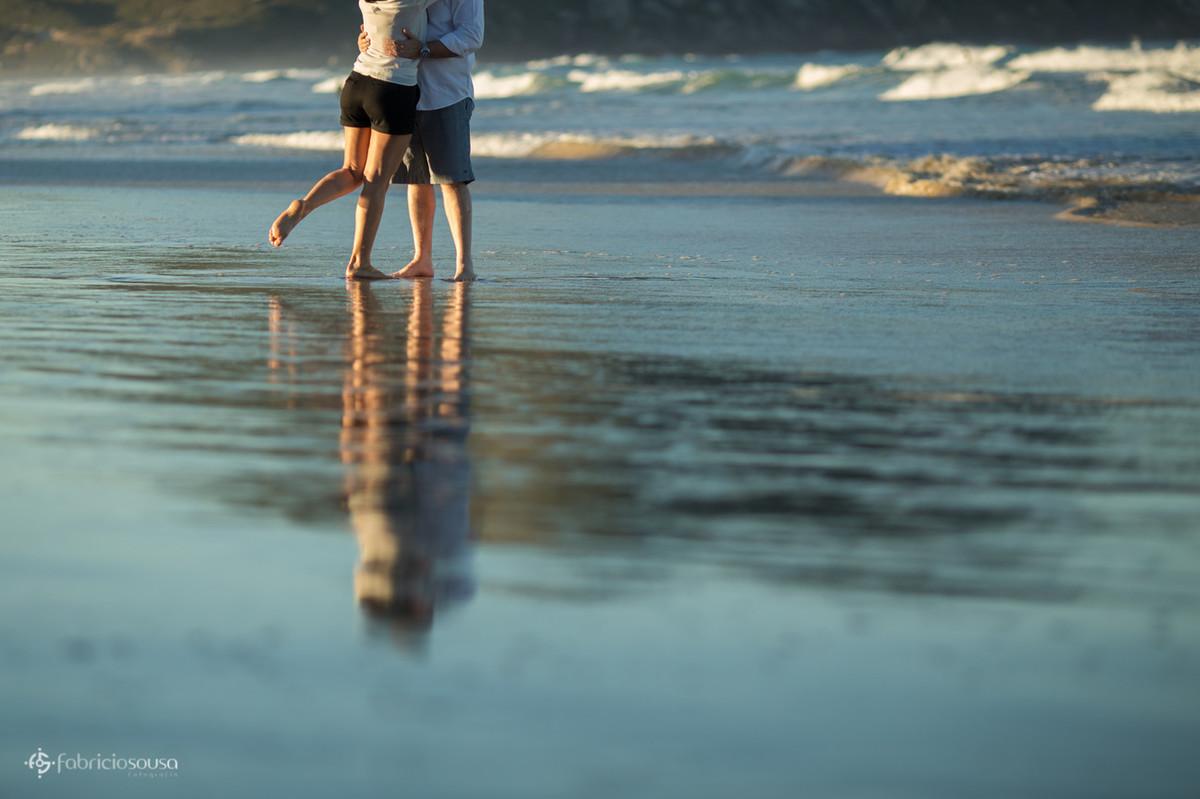 casal com o pé na areia da praia
