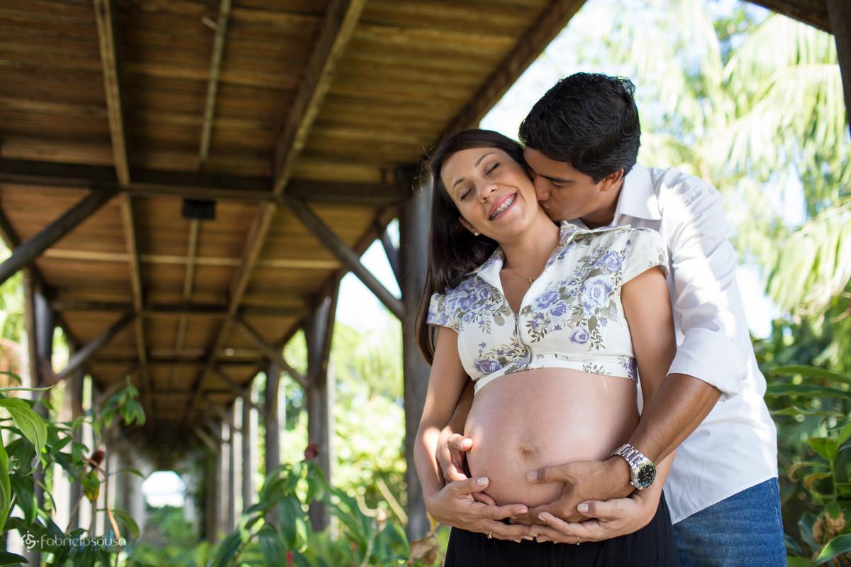Homem abraça mulher grávida por trás e beija o pescoço dela