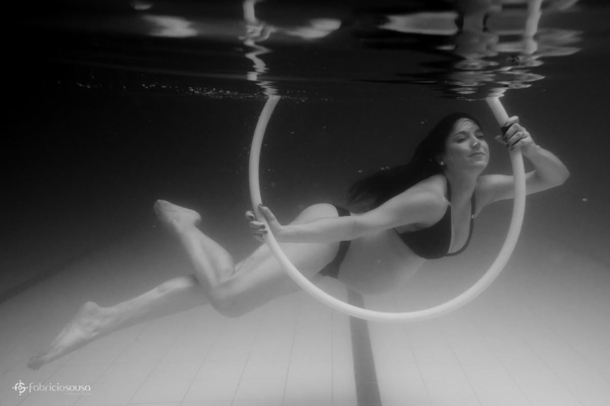Mulher gestante com bambolê embaixo da água