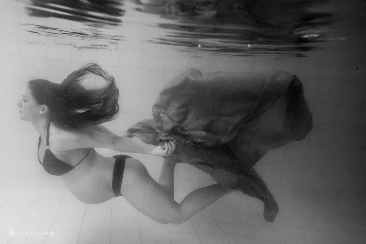 Mamãe grávida nada embaixo da água segurando tecido