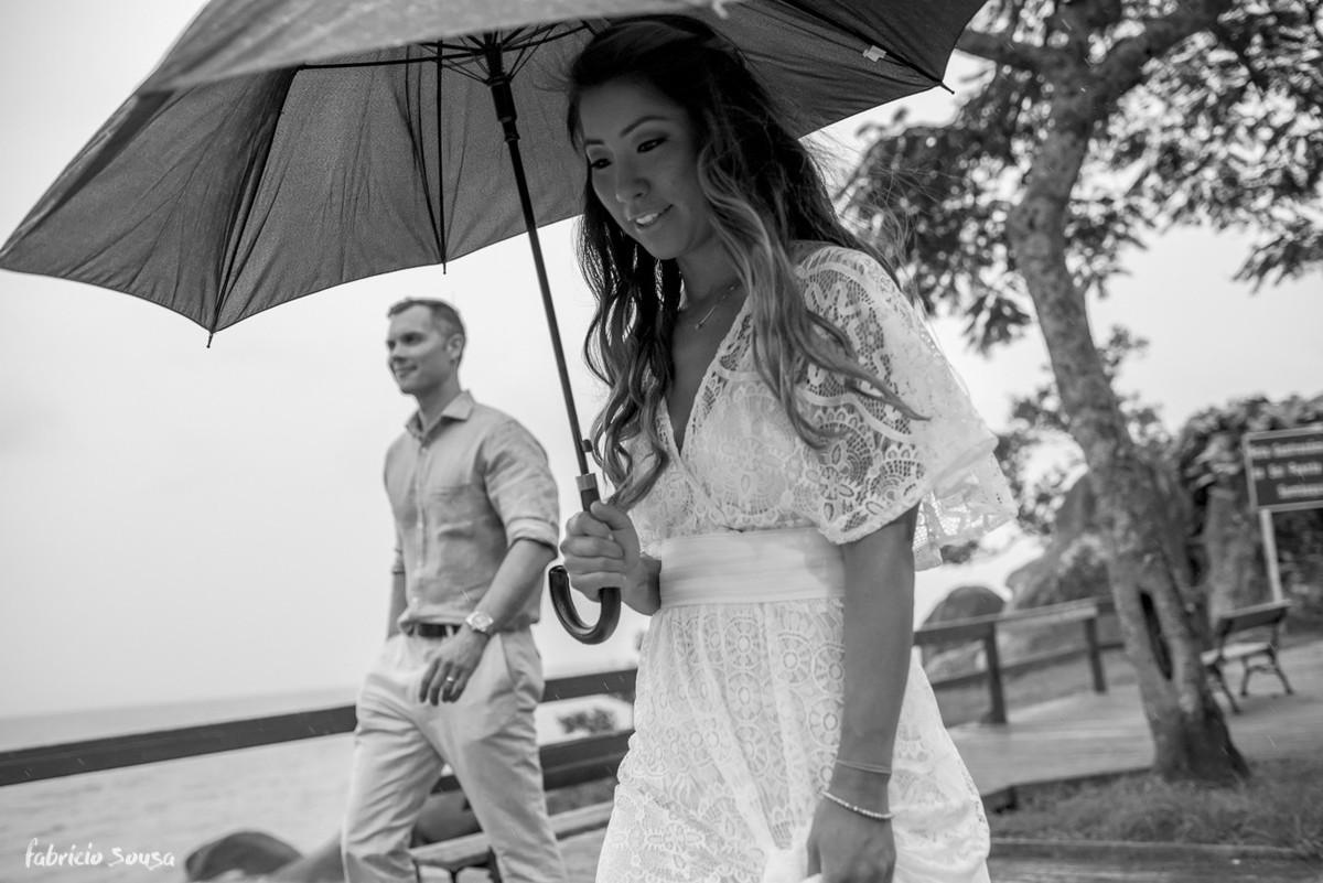 noiva caminha para festa com guarda-chuvas