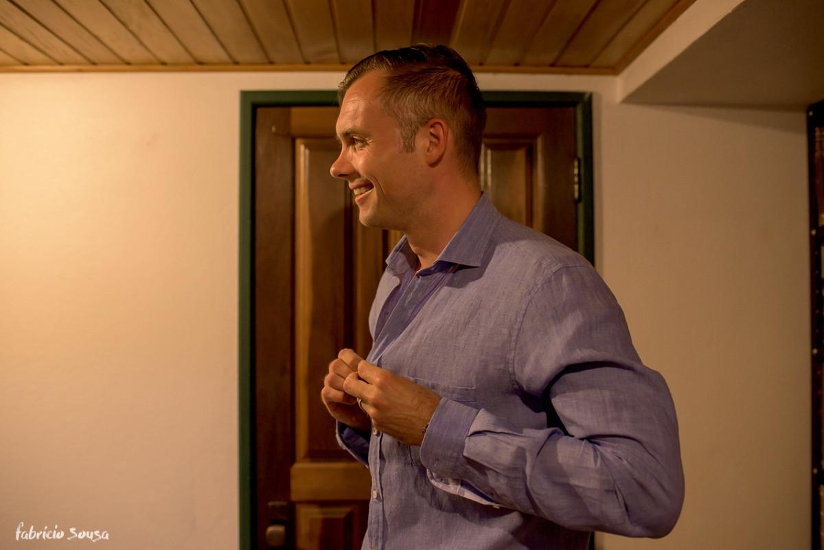 o noivo colocando a camisa no seu casamento