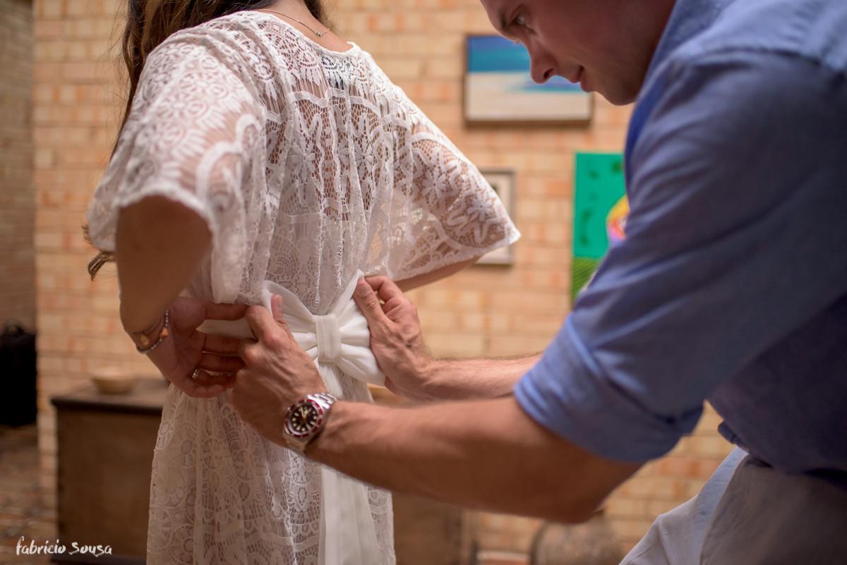 noivo ajuda noiva no detalhe do vestido
