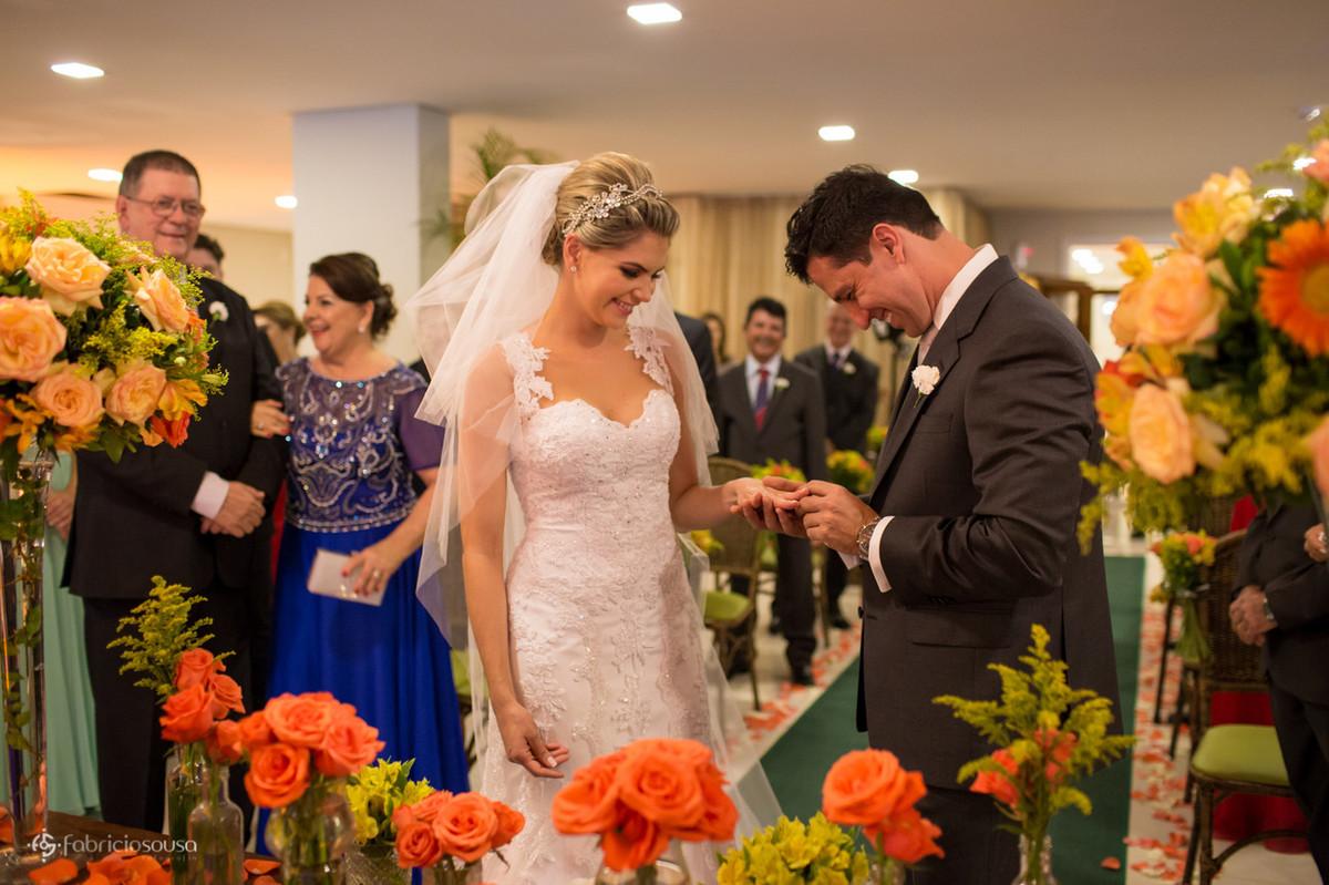 noivo coloca aliança e sorri para a noiva