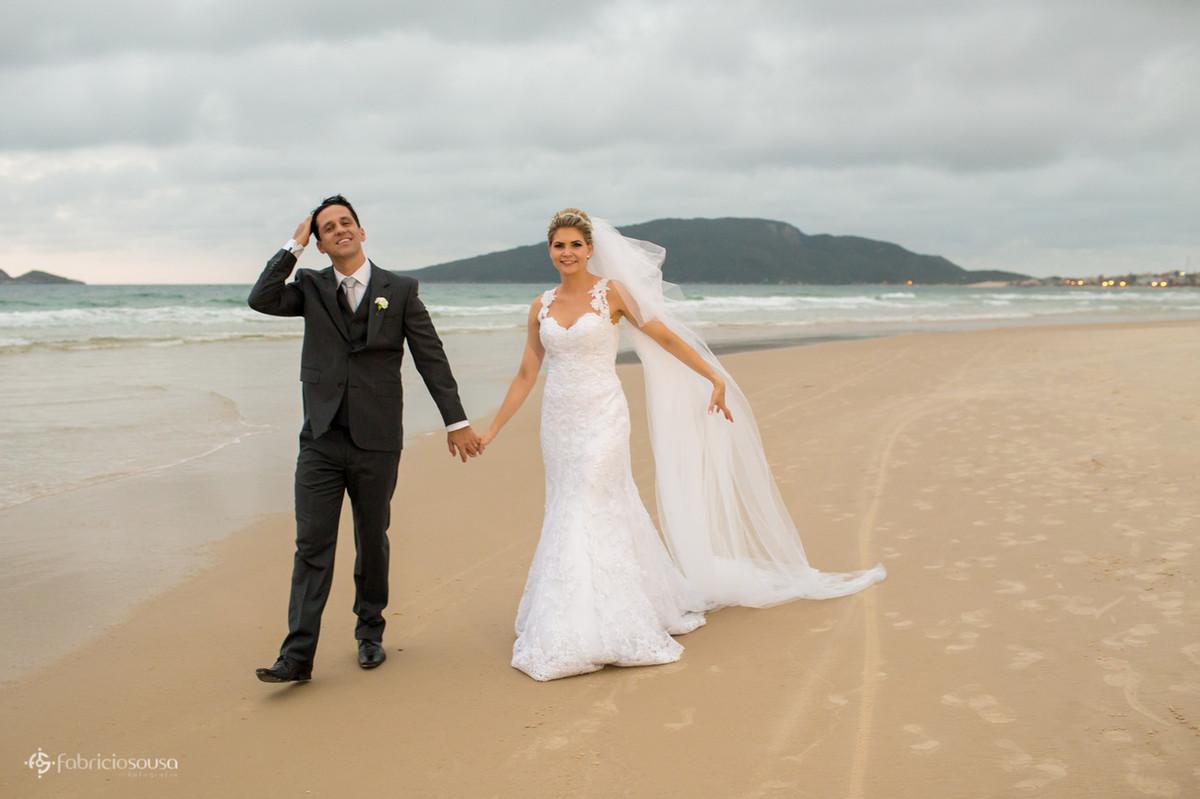 noivos caminham na areia da praia