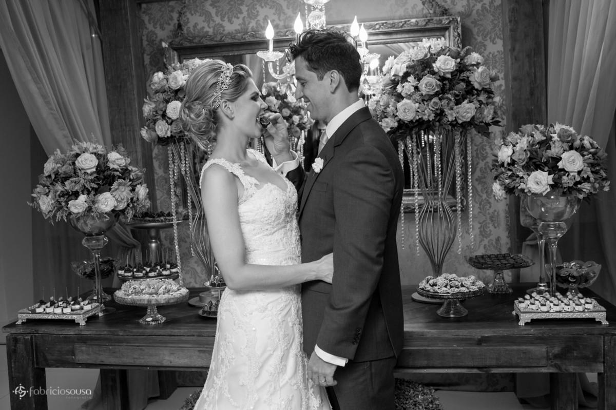 recem-casados em frente à mesa de doces