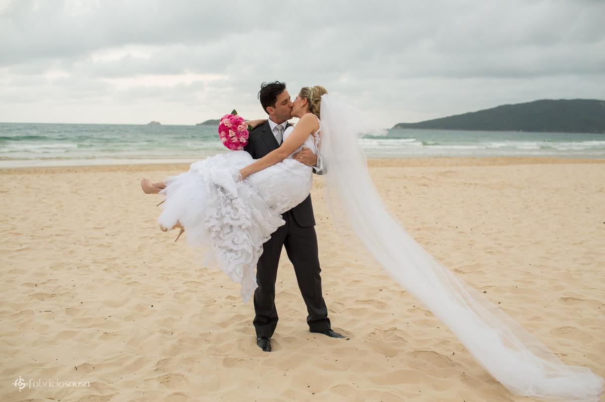 noivo carrega a noiva na praia dos ingleses - norte da ilha de Florianópolis