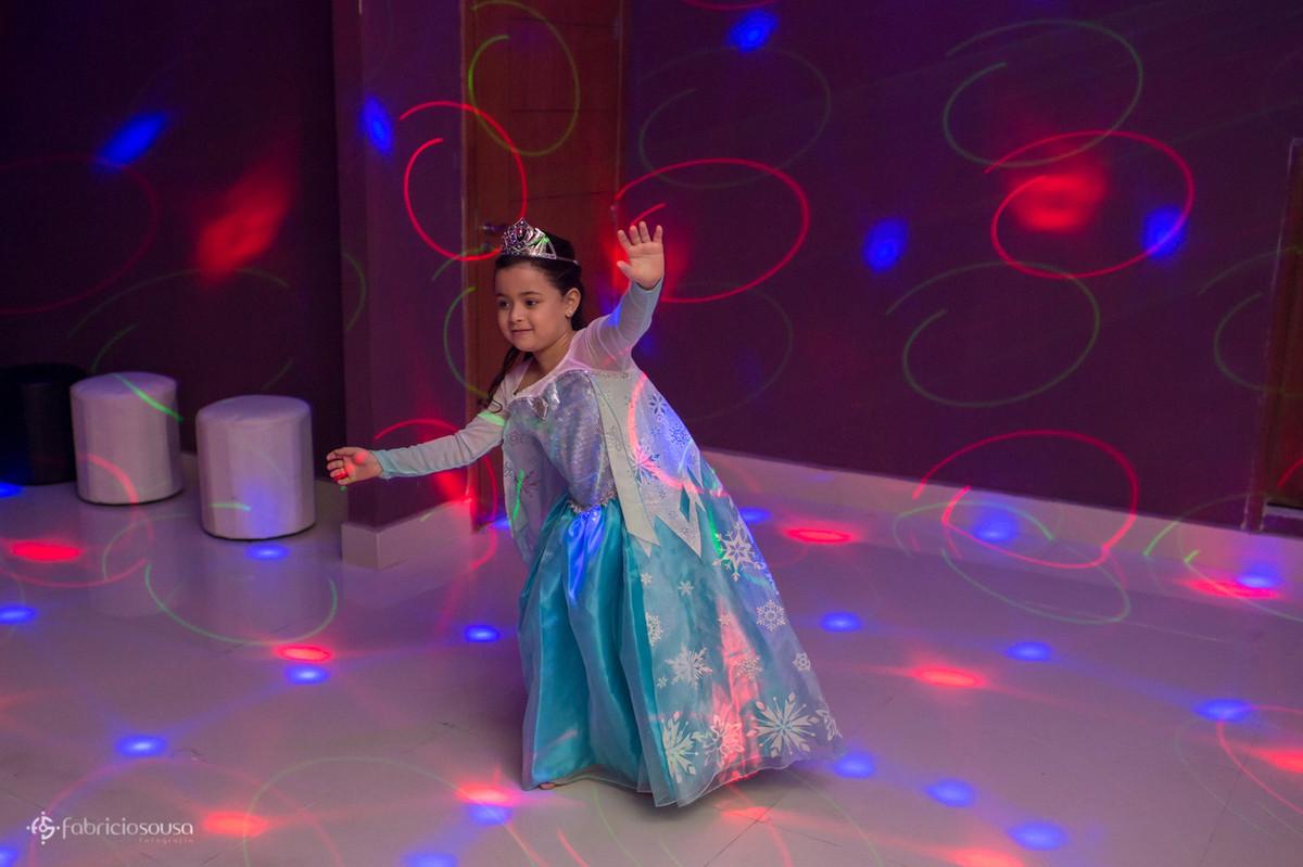 Menina com vestido de princesa dançando com as luzes do dj