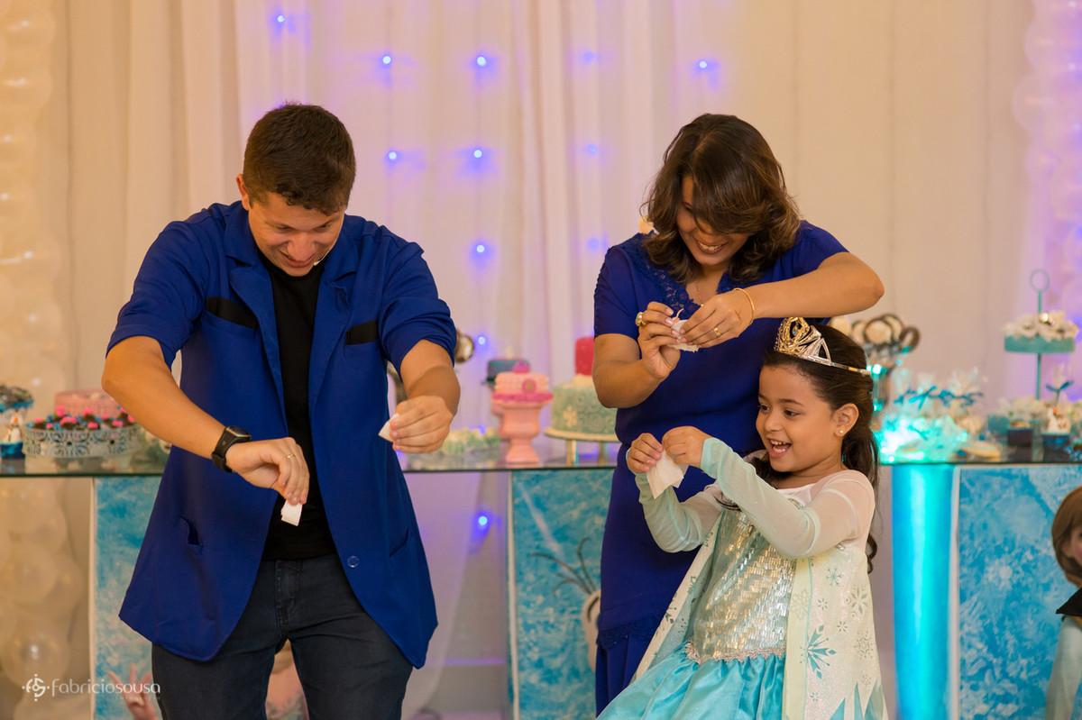 Mágico preparando truque com a aniversariante e mãe