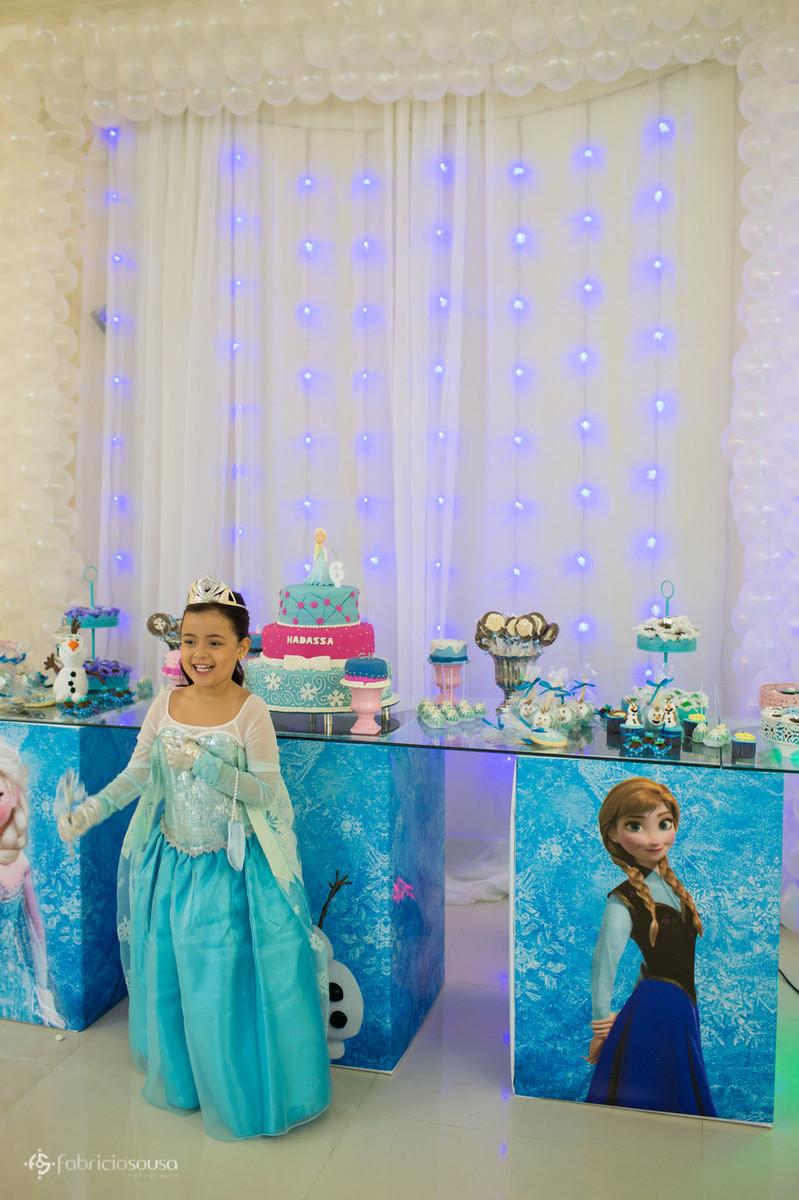 Posando em frente à mesa de doces com tema Frozen