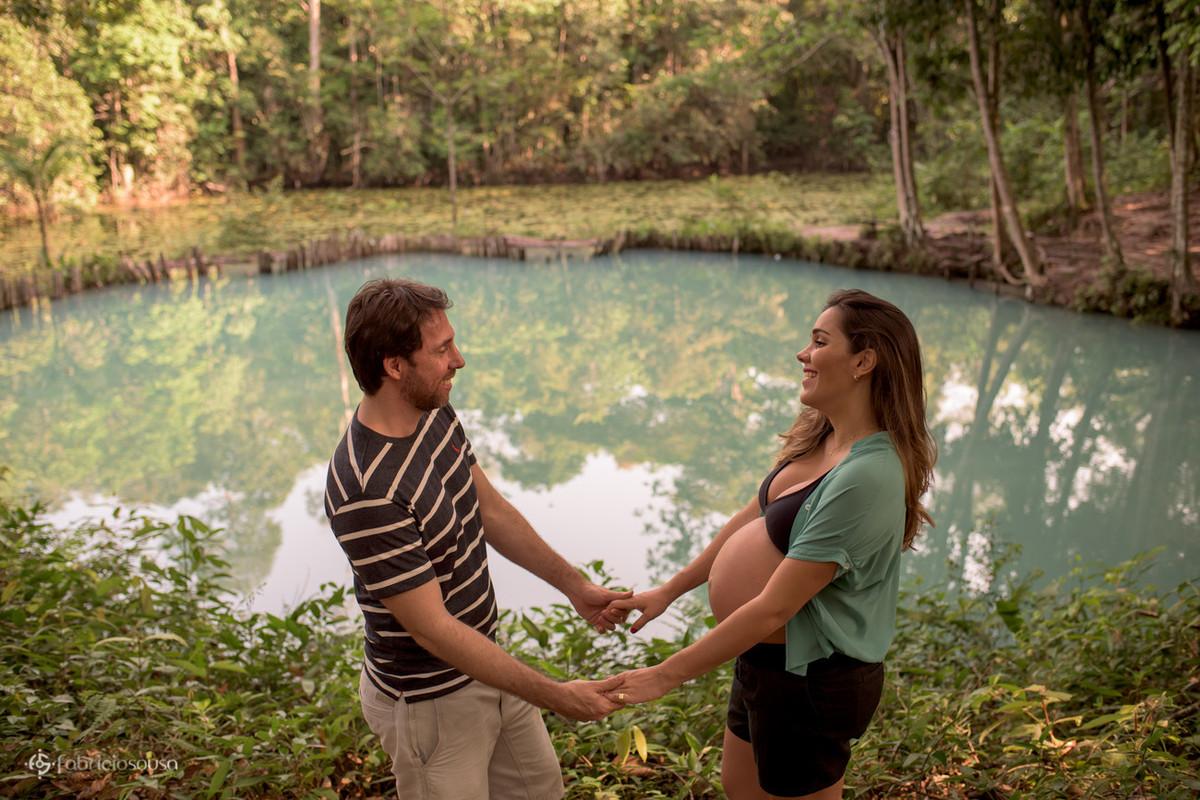casal grávido de mãos dadas e lago verde de fundo