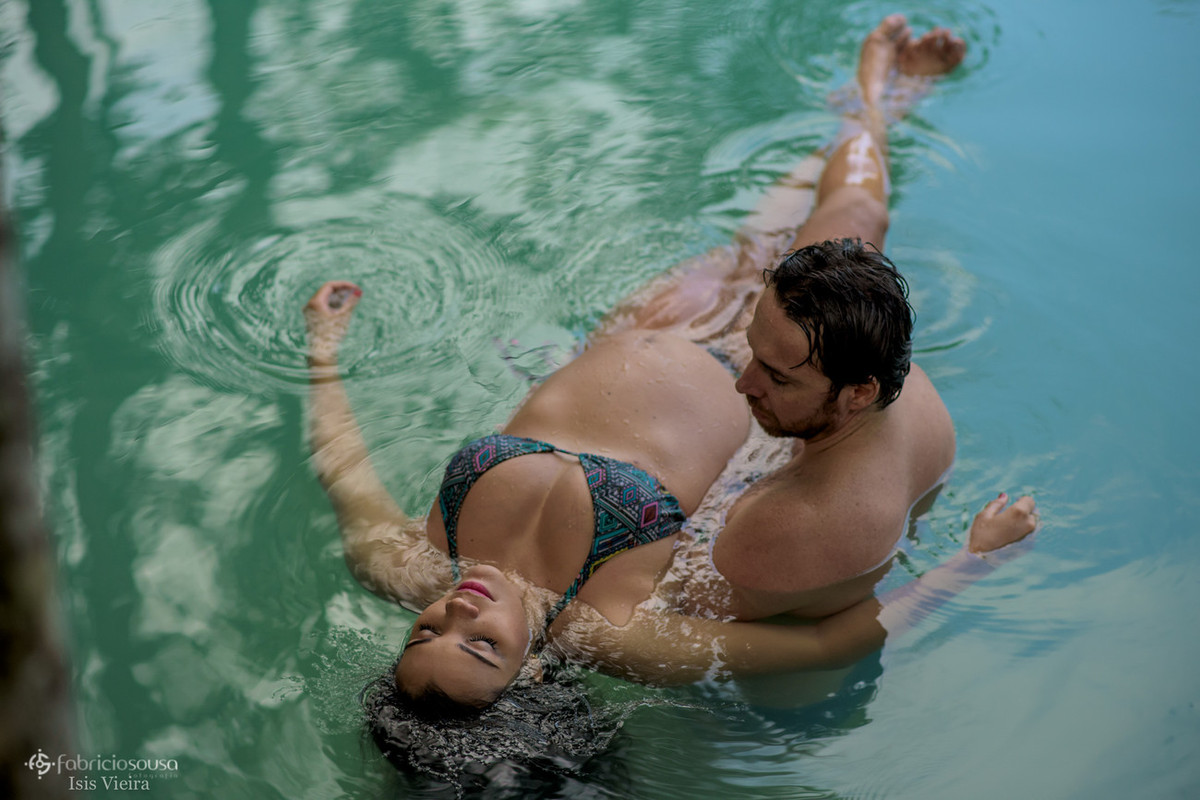 marido flutua com esposa grávida na água cristalina do igarapé