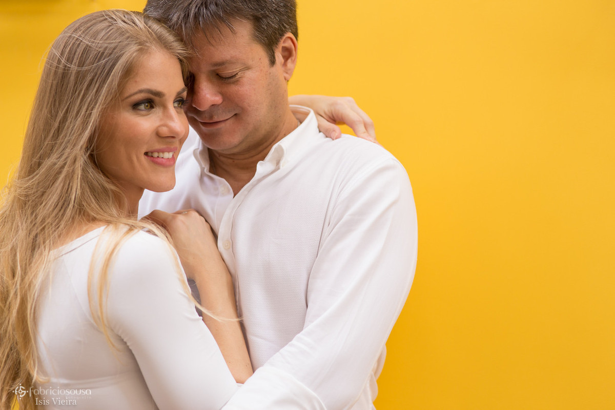 casal chamegando na parede amarela