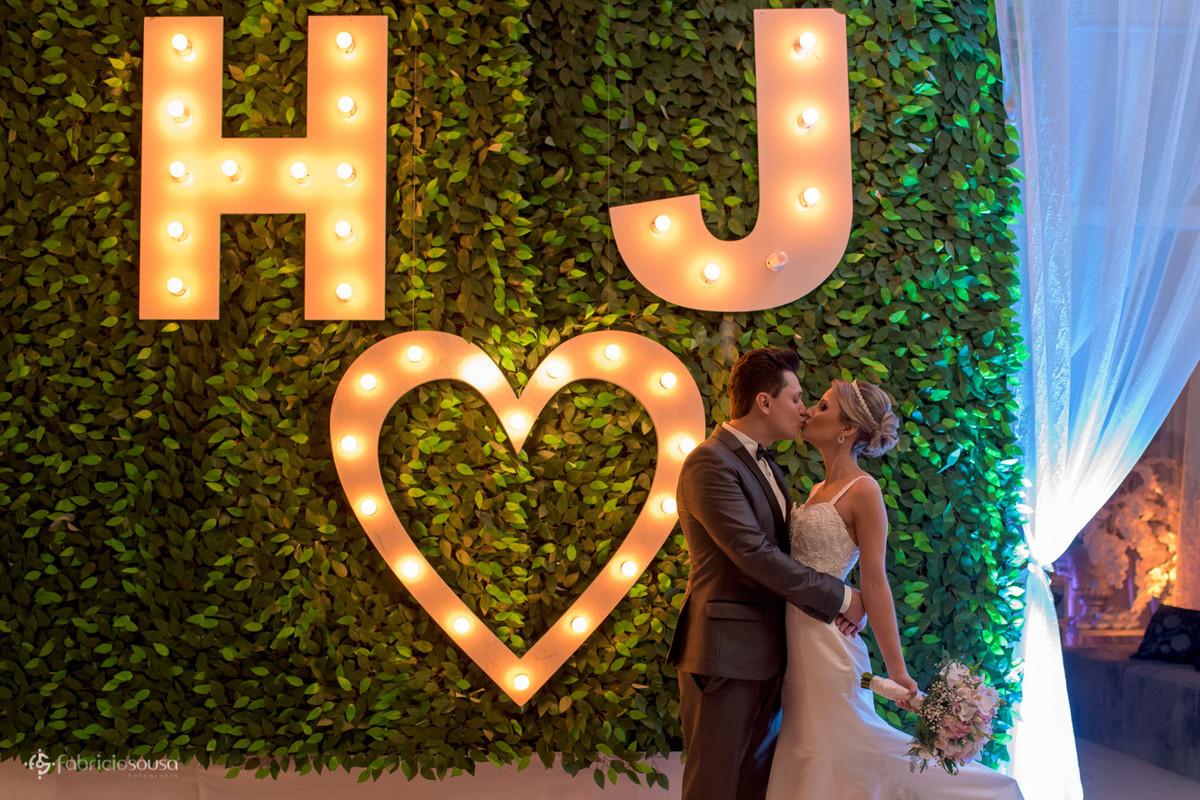 beijo com cerca viva e iniciais dos noivos e coração iluminado - muitas luzes amarelas
