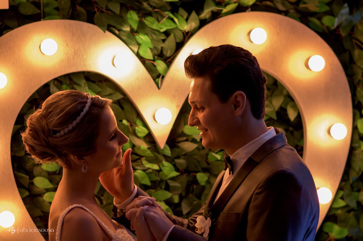 carícias dos noivos com luzes de coração no fundo
