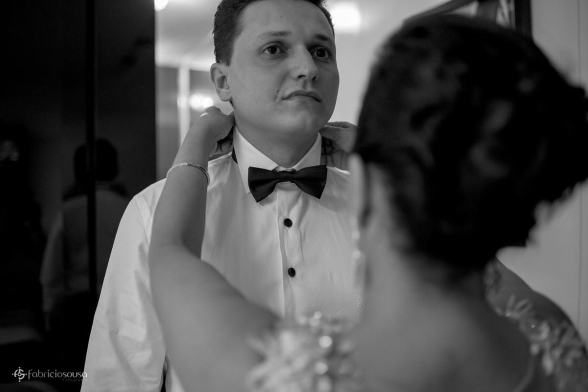 mãe colocando a gravata borboleta no noivo