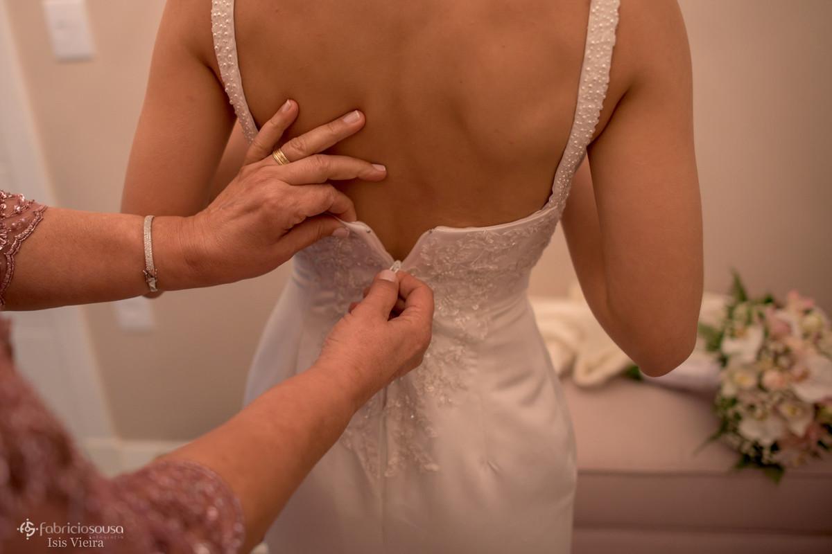 mãe fechando o vestido na noiva