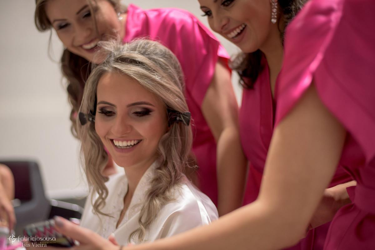 noiva e madrinhas conferindo fotos no celular