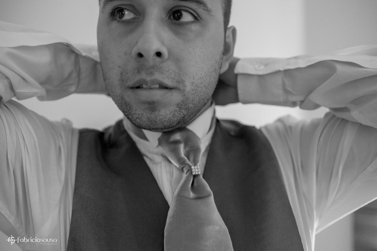 close do noivo colocando a gravata