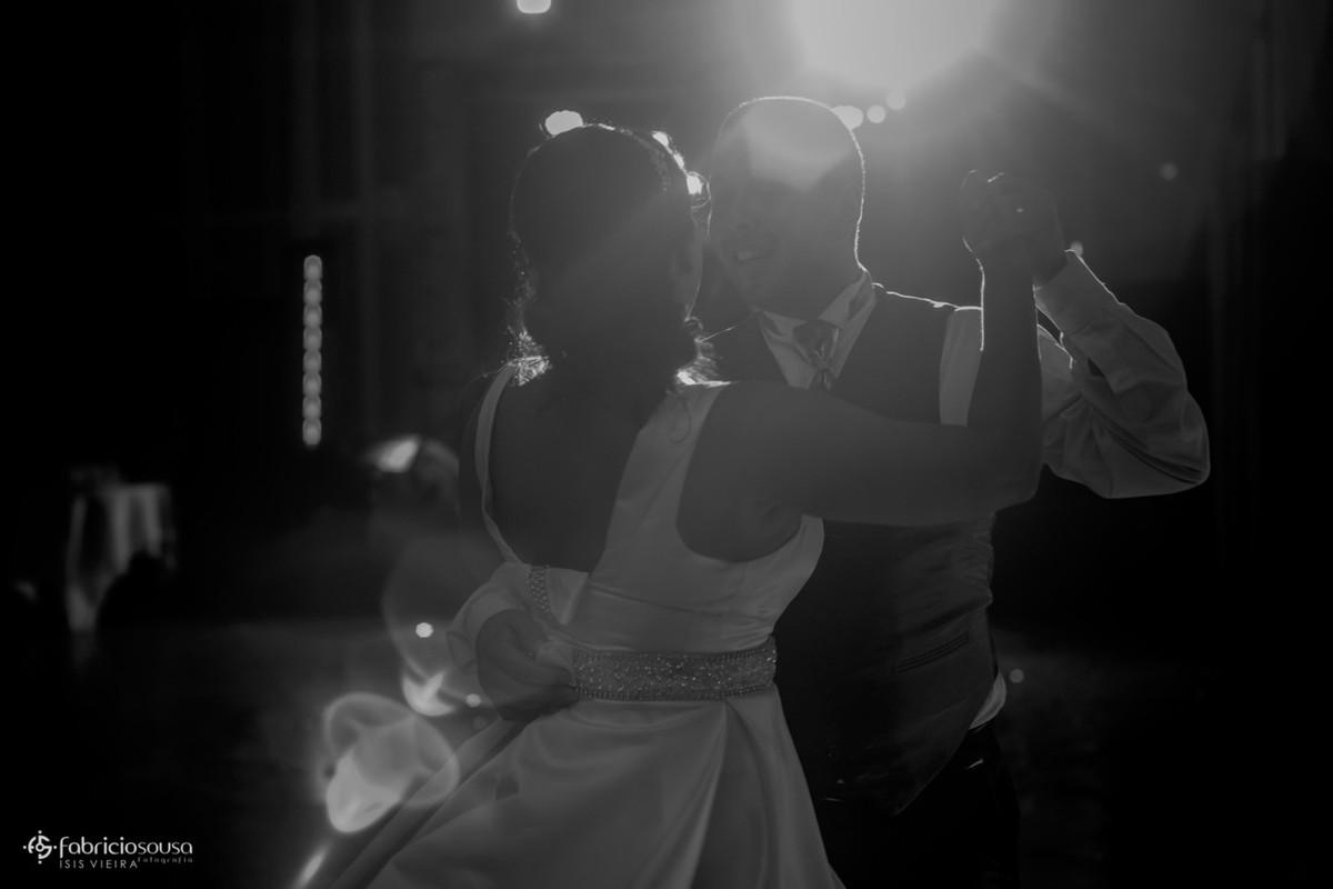 contraluz dos noivos dançando agarrados na pista