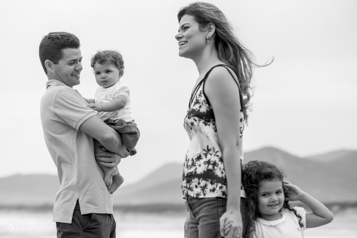 Pai com Maitê no colo e mãe de mãos dadas com Isabela bw